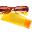 Sunglasses and sun lotion — Stock Photo