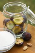 Glass with plums and sugar on garden table. — Stock Photo