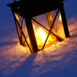 Lantern with burning candle on snow in the evening. — Stock Photo #27277717