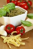 Pasta, basil pesto, tomatoe, garlic and parmesan cheese. — Stock Photo