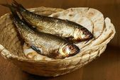 Loaves of bread and two fishes in a basket. — Stock Photo