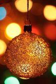Christmas ornament and defocused Christmas lights. — Stock Photo
