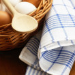 Basket with chicken eggs, wooden spoon and dishcloth — Stock Photo
