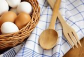 Detail of wicker basket with chicken eggs, wooden spoon, fork and dishcloth — Stock Photo