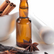 Vanilla beans, anise stars, mortar and baking flavor in a bottle — Stock Photo