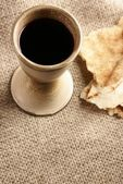 Chalice with wine and piece of bread — Stock Photo