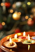 Candles in nutshells floating on water with Christmas background. — Stock Photo