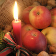 Candle, apples and walnuts in basket — Stock Photo