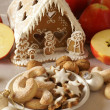 Gingerbread house, christmas cookies and apples — Stock Photo