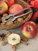 Mand met appels, walnoten en notenkraker. — Stockfoto