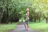 Sporty young woman stay barefoot in park after sport excises. — Stock Photo