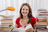Studying happy young woman reading her book for school. — Stock Photo