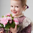 Portrait of a beautiful little girl in retro dress with bouquet of flowers. Cute girl is smelling flowers. Studio shot. Gray background. Greeting Card — Foto de Stock