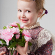 Portrait of a beautiful little girl in retro dress with bouquet of flowers. Cute girl is smelling flowers. Studio shot. Gray background. Greeting Card — Stock Photo