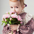 Portrait of a beautiful little girl in retro dress with bouquet of flowers. Cute girl is smelling flowers. Studio shot. Gray background. Greeting Card — Stock fotografie