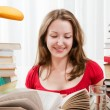 Smart female college student studying with books in bright light room. Pretty female working with a lot of books — Stock Photo