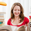 Stock Photo: Smart female college student studying with books in bright light room. Pretty female working with lot of books
