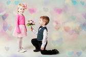 Little boy kneels on one knee giving flowers to girl. Hearts bokeh background. st valentine's day present. Romantic gift — Stock Photo