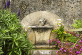 Ancient old fountain with flowers around. Source of water — Stock Photo