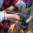 Woman working at the weaving loom. Traditional Ethnic clothes of Baltic. — Stock Photo #48115771