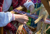 Woman working at the weaving loom. Traditional Ethnic clothes of Baltic. — Stockfoto