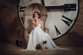A smiling girl in a wedding dress in strange chair. The bride in a chair on the background of clocks and fireplace tool set. Horizontal — Foto de Stock