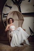 A smiling girl in a wedding dress in strange chair. Vintage toned. — Stock Photo