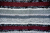 Strip woven red and gray rug surface close up.  — Photo