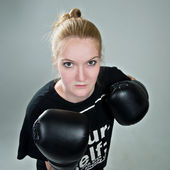 Aggressive teenager girl with box gloves on the grey background. — Stock Photo