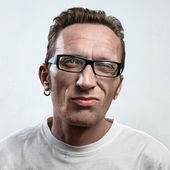 Portrait unsatisfied man with an earring in a white t-shirt on light gray background. face close up.  — Stock Photo