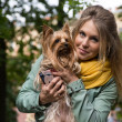 Young smiling pretty blonde woman in city park. Small yorkshire terrier is on her hands. — Stock Photo