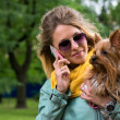 Young smiling pretty blonde woman talking mobile phone. Small yorkshire terrier is on her hands. — Stock Photo #49055417