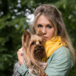 Young sad pretty blonde woman in city park. Small yorkshire terrier is on her hands. — Stock Photo