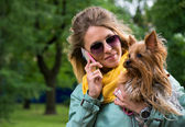 Young smiling pretty blonde woman talking mobile phone. Small yorkshire terrier is on her hands. — Stock Photo