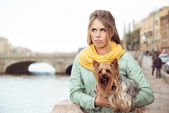 Sad young woman with small dog on the embarkment, waiting friend. — Stock Photo