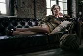 Fashion glamour girl lying on a black leather sofa — Stock Photo