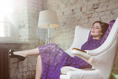 Fashion glamour girl dreamily sitting in white chair — Stock Photo
