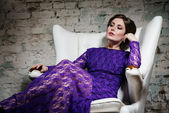 Fashion glamour girl dreamily sitting in white chair in violet lace dress — Stock Photo