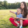 Mother and child playing at the grass. naughty boy crying and and point by his finger. — Stock Photo