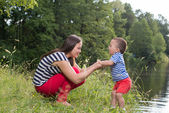 Outdoor park happy young mother and son playing — Stock Photo