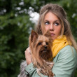 Young sad pretty blonde woman in city park with her dog — Foto de Stock
