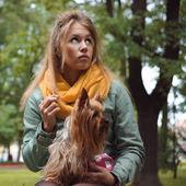 Sad girl with dog waiting boyfriend in city park — Stock Photo