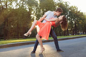 Happy young couple in love dancing in the sunset light on the street — Stock Photo