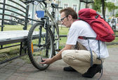 Man pump up the bike wheel on the street — Stock Photo