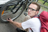 Man pump up the bike wheel outdoor on the city street — Stock Photo