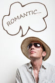 Young man in straw hat and sunglasses dreaming of the romantic — Stock Photo