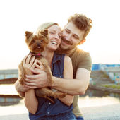 Laughing young couple with small dog in sunset light — Stock Photo