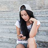 Slim teenage girl with long black hair sits on the stairs in mall and listen music on her smartphone. — Stock Photo