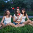 Three happy girlfriends on a picnic with lollipops in shape of heart, in short shorts and white T-shirts sit on the grass in the late evening, and smiling — Stock Photo #51305943
