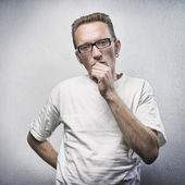 Thinking man on gray textured background. Portrait of a casual young pensive man looking into camera and gnaw nails. — Stock Photo